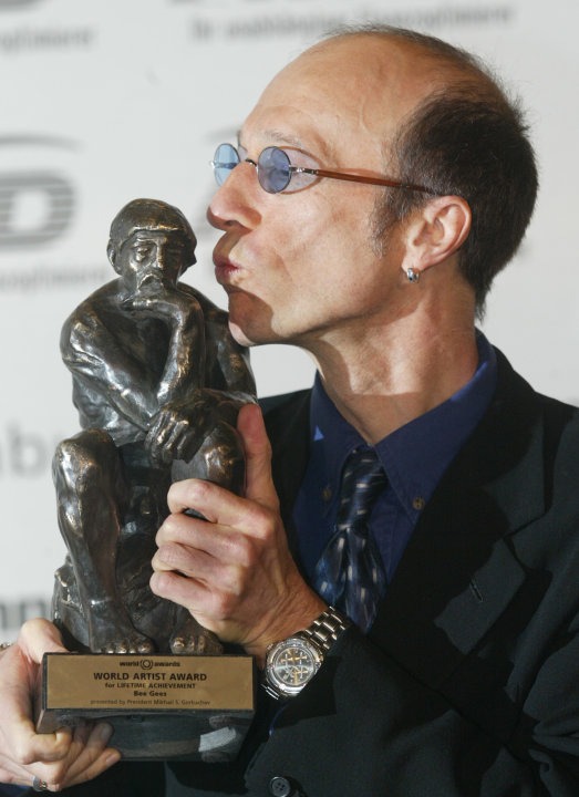 FILE - In this Oct. 22, 2003, file photo, musician Robin Gibb of The Bee Gees kisses his prize after he received it at the World Award ceremony in Hamburg, Germany. A representative said on Sunday, Ma
