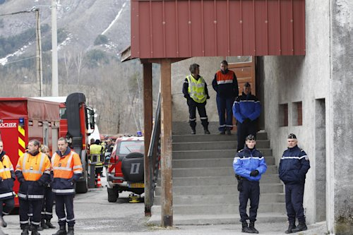 Rescue workers and security officers guard the makeshift morgue prepared for the 150 victims who died in a Germanwings plane crash in the French Alps,...