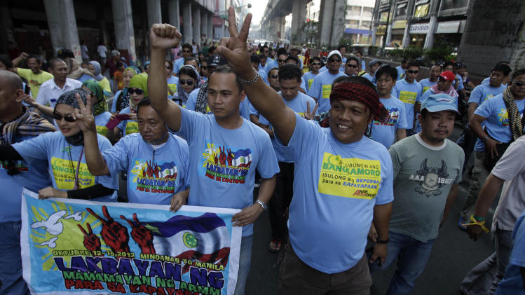 Filipino Muslim men and supporters march as they join a rally in support of a preliminary peace agreement between the government and the nation's largest Muslim rebel group outside the Malacanang presidential palace in Manila, Philippines, on Sunday Oct. 14, 2012. About 200 Muslim rebels led by their elusive chief arrived in the Philippine capital on Sunday for the signing of a preliminary peace pact aimed at ending one of Asia's longest-running insurgencies. (AP Photo/Aaron Favila)