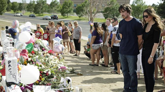"Actor Christian Bale and his wife Sibi Blazic visit a memorial to the victims of Friday's mass shooting, Tuesday, July 24, 2012, in Aurora, Colo. Twelve people were killed when a gunman opened fire during a late-night showing of the movie ""The Dark Knight Rises,"" which stars Bale as Batman. (AP Photo/Ted S. Warren)"