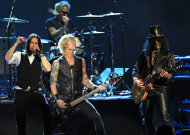 Guns N' Roses' Duff McKagan, center and Slash, right, perform with guest vocalist Myles Kennedy, left, after induction into the Rock and Roll Hall of Fame Saturday, April 14, 2012, in Cleveland. (AP Photo/Tony Dejak)