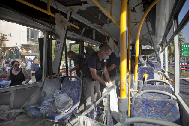 Israeli police officers examine a destroyed bus at the site of a bombing in Tel Aviv, Israel, Wednesday, Nov. 21, 2012. A bomb ripped through an Israeli bus near the nation's military headquarters in