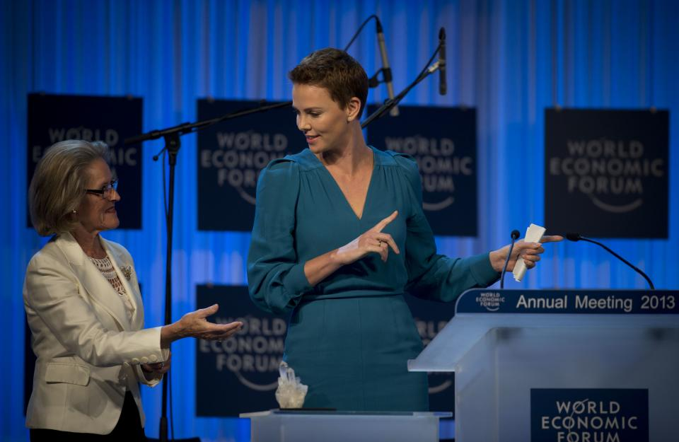 South African Academy Award-winning actress Charlize Theron, right, gestures as she  accepts her Crystal award from Hilde Schwab on the eve of the opening of the 43rd Annual Meeting of the World Economic Forum, WEF, in Davos, Switzerland, Tuesday, Jan. 22, 2013.  (AP Photo/Anja Niedringhaus)