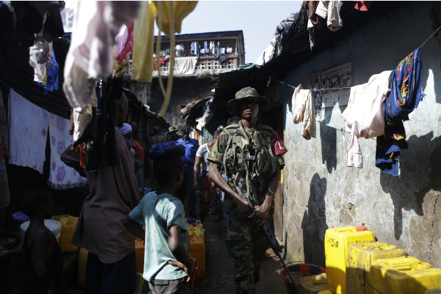 Security forces walk through the Mabella slum after breaking up a domestic dispute and arresting several residents, in Freetown, Sierra Leone Friday, Nov. 16, 2012. Ten years after the end of a devast