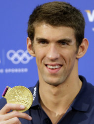 United States swimmer Michael Phelps holds up one of his gold medals during a news conference at the 2012 Summer Olympics, London, Sunday, Aug. 5, 2012. (AP Photo/Kirsty Wigglesworth)