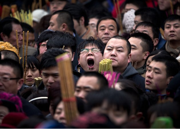 A Chinese man, center, yawns as he and other worshippers gather to pray on the first day of Chinese Lunar New Year at Yonghegong Lama Temple in Beijing Sunday, Feb. 10, 2013. Millions across China are