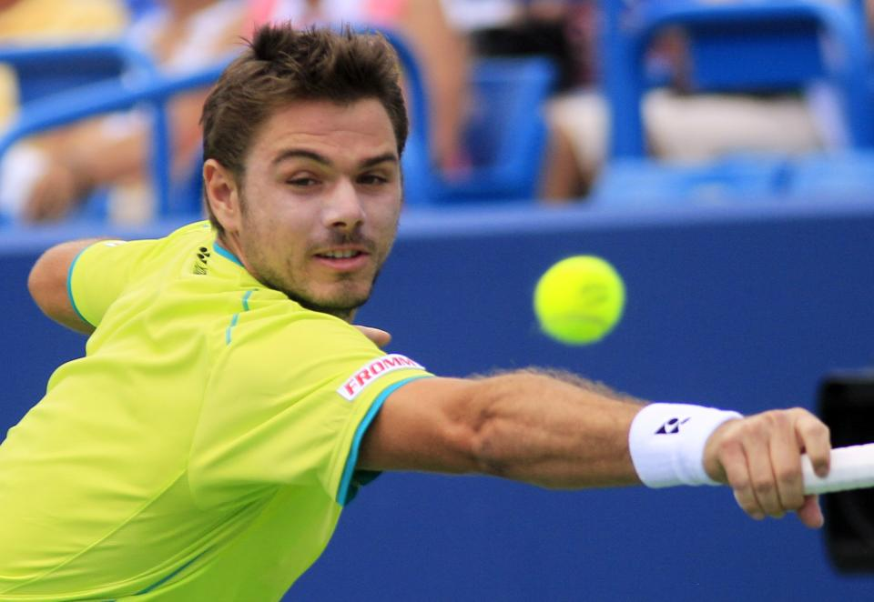 Stanislas Wawrinka, from Switzerland, returns a service against Roger Federer, from Switzerland, during a semifinal match at the Western & Southern Open tennis tournament, Saturday, Aug. 18, 2012, in Mason, Ohio. (AP Photo/Al Behrman)