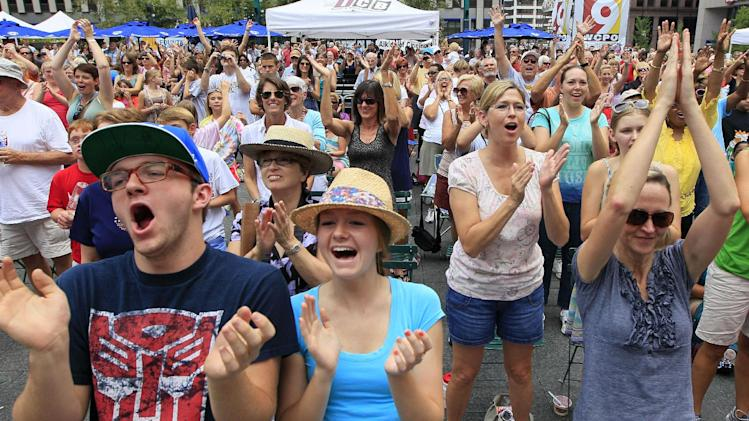 In this Thursday, July 12, 2012 photo, hundreds of people applaud a choir performing, on Fountain Square in Cincinnati. Hundreds of choirs from around the world are competing in 23 categories in the event that ends Saturday. (AP Photo/Al Behrman)