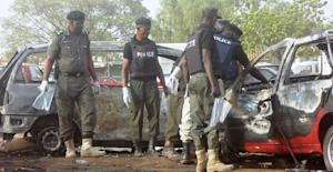 Police bomb experts sweep the scene of a twin suicide…