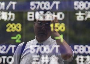 A man wipes his head as he is reflected on a stock quotation board outside a brokerage in Tokyo
