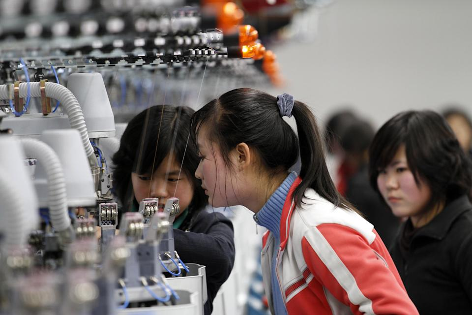 In this Jan. 30, 2012 photo, women work with machines inside a factory that produces stockings in Pyongyang, North Korea. (AP Photo/Kim Kwang Hyon)
