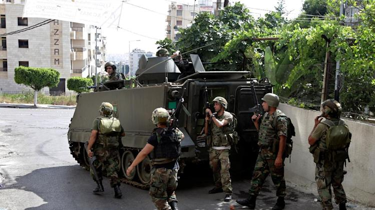 Lebanese army soldiers raid homes to search for gunmen after clashes that erupted between followers of a radical Sunni cleric Sheik Ahmad al-Assir and Shiite gunmen, in the southern port city of Sidon, Lebanon, Monday, June 24, 2013. Lebanese troops battled heavily armed followers of a hard-line Sunni cleric holed up in a mosque complex in a southern port city on Monday, the second day of fighting that has left more than a dozen of soldiers dead, the military said. (AP Photo/Bilal Hussein)