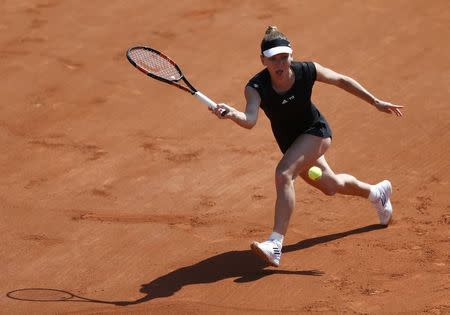 Simona Halep of Romania plays a shot to Evgeniya Rodina of Russia during their women's singles match at the French Open tennis tournament at the Roland Garros stadium in Paris