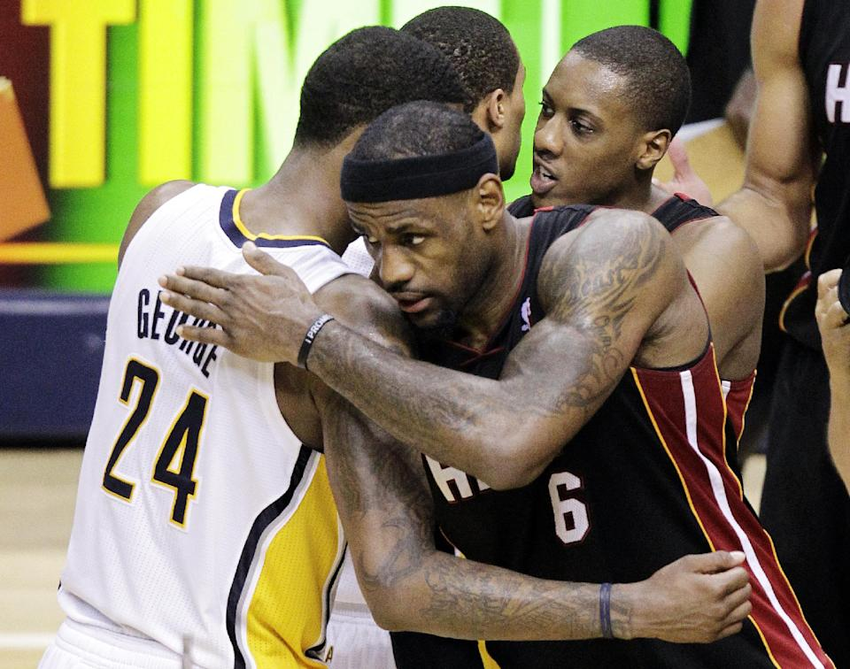Miami Heat forward LeBron James, right, hugs Indiana Pacers guard Paul George as they leave the court following Game 6 in their NBA basketball Eastern Conference semifinal playoff series in Indianapolis, Thursday, May 24, 2012. The Heat defeated the Pacers 105-93 to win the series 4-2. (AP Photo/Michael Conroy)