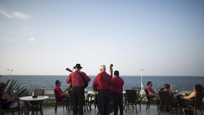 Musicians play traditional Cuban music as tourists enjoy the sunset from a hotel in Havana
