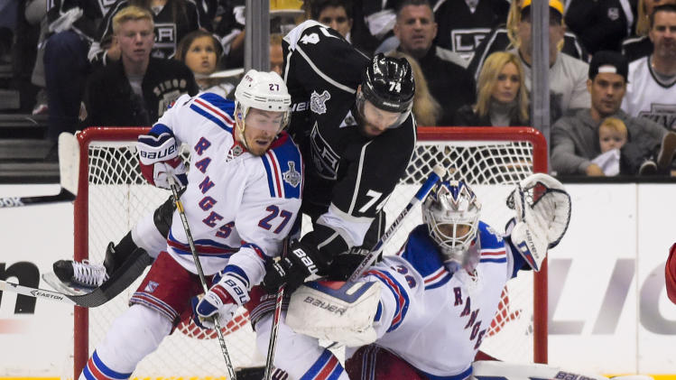 Los Angeles winger Dwight King scores on the Rangers while battling defenseman Ryan McDonagh and coming into contact with goalie Henrik Lundqvist in Game 2 of the 2014 Stanley Cup final. (AP)