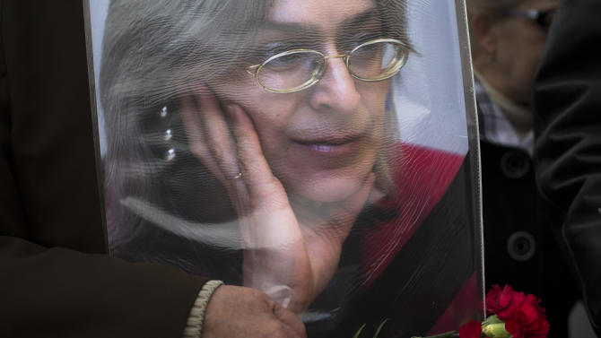 An elderly woman holds a portrait of slain journalist Anna Politkovskaya,during a rally in downtown Moscow, Sunday, Oct. 7, 2012. About 200 people rallied Thursday on the 6th anniversary of the killing of Anna Politkovskaya, calling on the authorities to find and punish the killers of journalists and human rights activists in Russia. (AP Photo/Alexander Zemlianichenko)