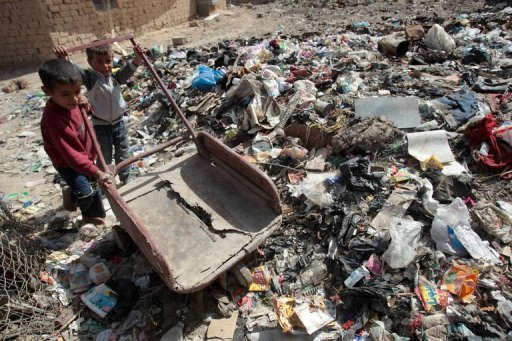 Iraqi children play on a garbage …