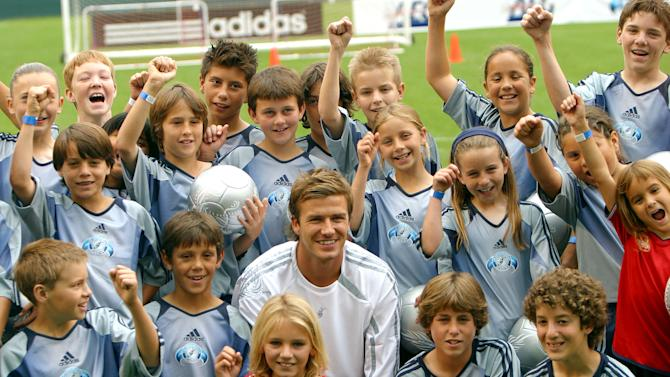 FILE - In this June 2, 2005, file photom soccer star David Beckham poses with kids from the Los Angeles area during a field skills demonstration following a news conference in Carson, Calif. The 38-year-old midfielder, who recently won a league title in a fourth country with Paris Saint-Germain, said Thursday, May 16, 2013, he will retire after the season.  (AP Photo/Stefano Paltera, File)