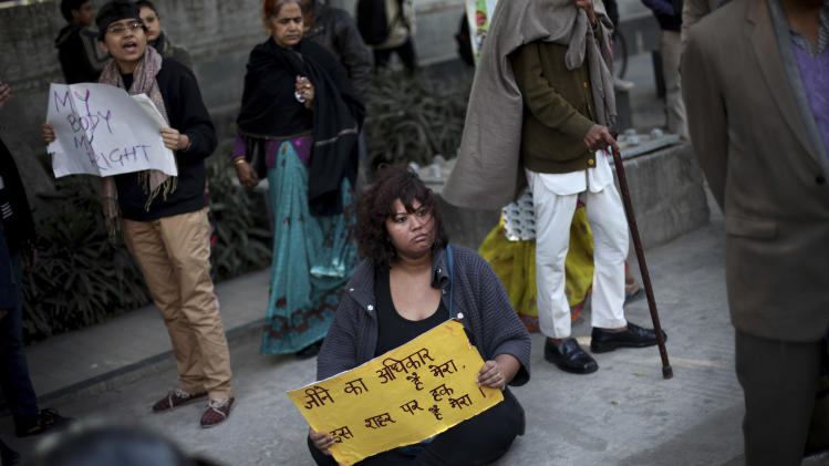 "An Indian protester holds a placard as she sits on a sidewalk during a protest in New Delhi, India, Wednesday, Dec. 19, 2012. The hours-long gang-rape and near fatal beating of a 23-year-old student on a bus in New Delhi triggered outrage and anger across the country Wednesday as Indians demanded action from authorities who have long ignored persistent violence and harassment against women. The placard reads  ""I have the right to live in the country."" (AP Photo/Altaf Qadri)"