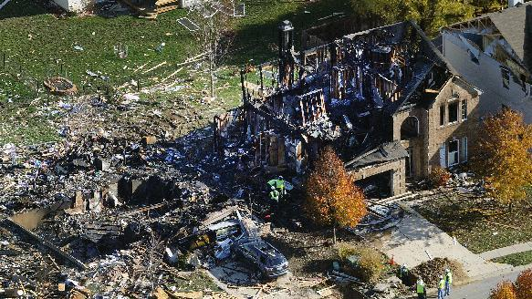 Citizens Energy workers continue their investigation Monday, Nov. 12, 2012, at the site of an explosion at a house in Indianapolis. The search for what caused a massive, deadly explosion that rocked an Indianapolis neighborhood turned to natural gas Monday, with officials checking gas lines and a homeowner saying a problem furnace could be to blame. (AP Photo/WTHR Chopper 13/The Indianapolis Star, Matt Kryger)