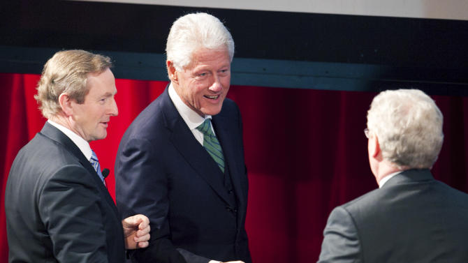 Former U.S. President Bill Clinton, center, is greeted by Irish Prime Minister Enda Kenny, left, and Deputy Prime Minister Eamon Gilmore, at the start of a conference hosted by New York University, Thursday, Feb. 9, 2012 in New York.  Clinton spoke to a group of New York business leaders about investing in Ireland. (AP Photo/Mark Lennihan)