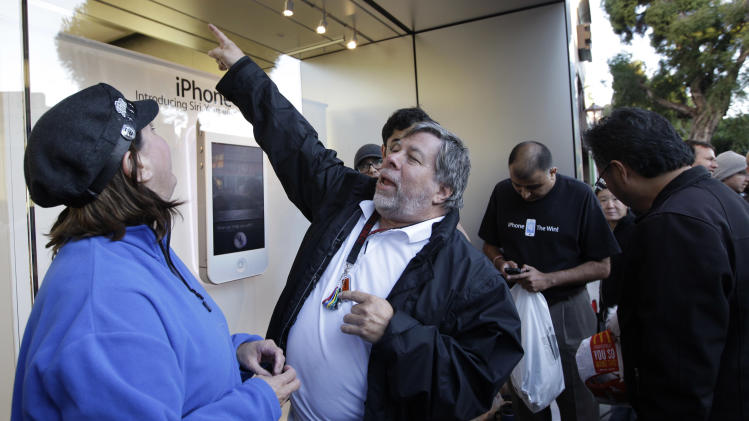 Apple co-founder Steve Wozniak points the way into an Apple store to buy a new Apple iPhone 4S in Los Gatos, Calif., Friday, Oct. 14, 2011. Wozniak waited 20 hours in line to be the first Apple customer at the Los Gatos Apple store to buy the new iPhone. (AP Photo/Paul Sakuma)