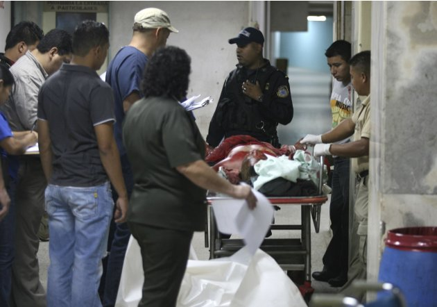 Police, doctors and forensic technicians stand next to a stretcher with the dead body of an inmate at the Hospital Escuela in Tegucigalpa