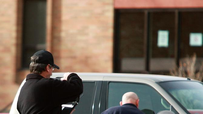 Casper Police officers check and photograph vehicles at the scene of a reported homicide at Casper College on Friday morning, Nov. 30, 2012, in Casper, Wyo. At least one person was killed and another was wounded Friday in an attack at Casper College, a community college in central Wyoming. It happened around 9 a.m., said school spokesman Rich Fujita.  (AP Photo/Casper Star-Tribune, Alan Rogers) MANDATORY CREDIT  TRIB.COM