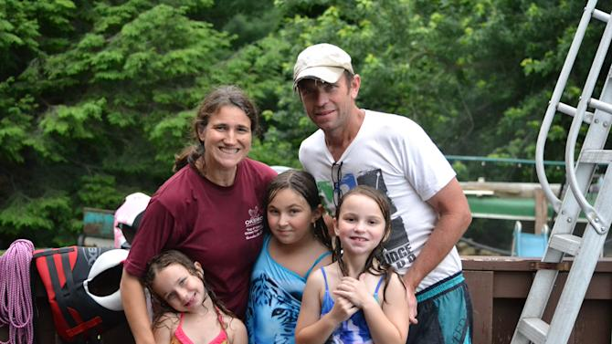"""This June 20, 2015 photo provided by Amy McKearney shows, parents, Amy and Scott McKearney, with their children, from left, Diane, 4, Kelley, 9, and Meghan, 7, at their home in Thomaston, Conn. """"I'm definitely not a helicopter parent but I'm not a free-range parent, either,"""" she said. While she's still on chauffeur duty to distance and busy roads, McKearney has found lots of little ways to foster growing independence in her brood. (Amy McKearney via AP)"""