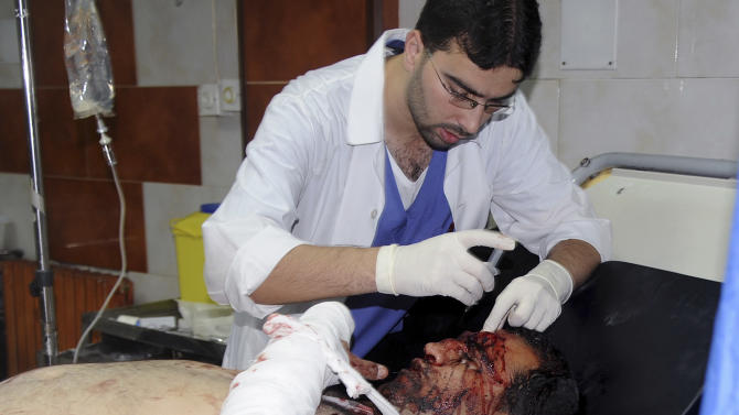 In this photo released by the Syrian official news agency SANA, a Syrian doctor treats an injured man who was wounded by a car bomb, at Jaramana neighborhood, in Damascus, Syria, Monday Oct. 29, 2012. A Syrian government official says a car bomb in a Damascus suburb has killed 10 people. The official said the blast on Monday in Jaramana also wounded 41 people and caused heavy damage. He spoke on condition of anonymity because he was not authorized to speak to the media. (AP Photo/SANA)