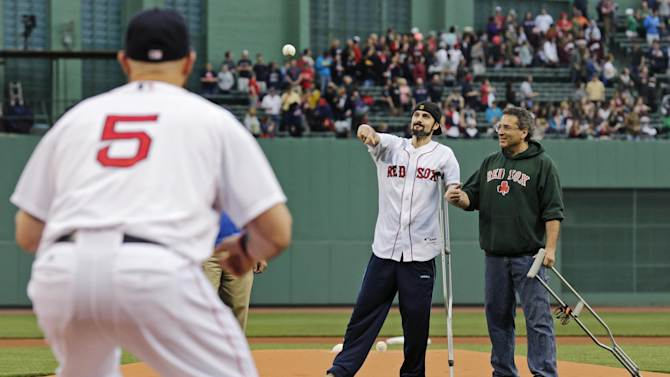 "In this Thursday, May 23, 2013 photo, Boston Marathon bombing survivor Pete DiMartino, of Rochester, N.Y., holds onto his dad, David, as he throws the ceremonial first pitch to Boston Red Sox left fielder Jonny Gomes (5) prior to a baseball game at Fenway Park in Boston. DiMartino was injured in an explosion near the finish line of the Boston Marathon. ""I don't want anybody feeling sorry for me,"" he said. ""... I want people to see that this has made me a better person and I want people to become better people through what they see through me."" (AP Photo/Charles Krupa)"