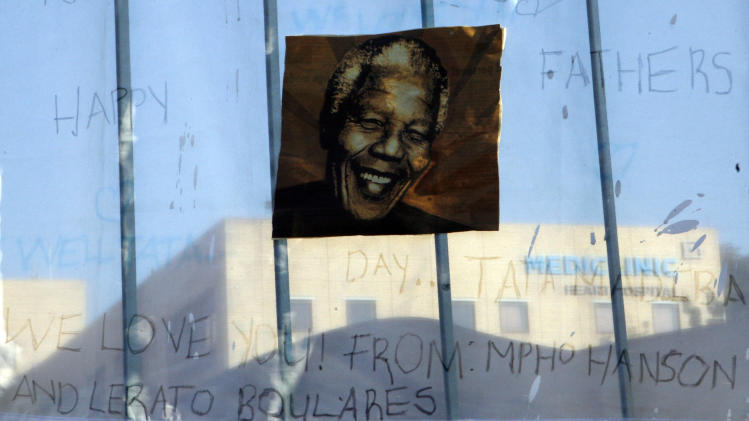 A print of Nelson Mandela and get-well messages hanged outside of the Mediclinic Heart Hospital where former South African President Nelson Mandela is being treated in Pretoria, South Africa Monday, June 24, 2013. Mandela's health has deteriorated and he is now in critical condition, the South African government said. (AP Photo/Themba Hadebe)
