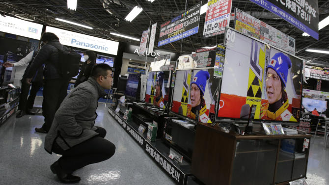 In this Wednesday, Feb. 19, 2014, photo, a shopper at an electronics store in Tokyo watches televisions showing recorded footage from an interview with Japanese ski jumper Noriaki Kasai, who won the silver medal in the large hill and the bronze in team ski jumping at the Sochi Olympics. The program is typical of the localized TV broadcasts in countries throughout the world during the Winter Olympics. (AP Photo/Shizuo Kambayashi)