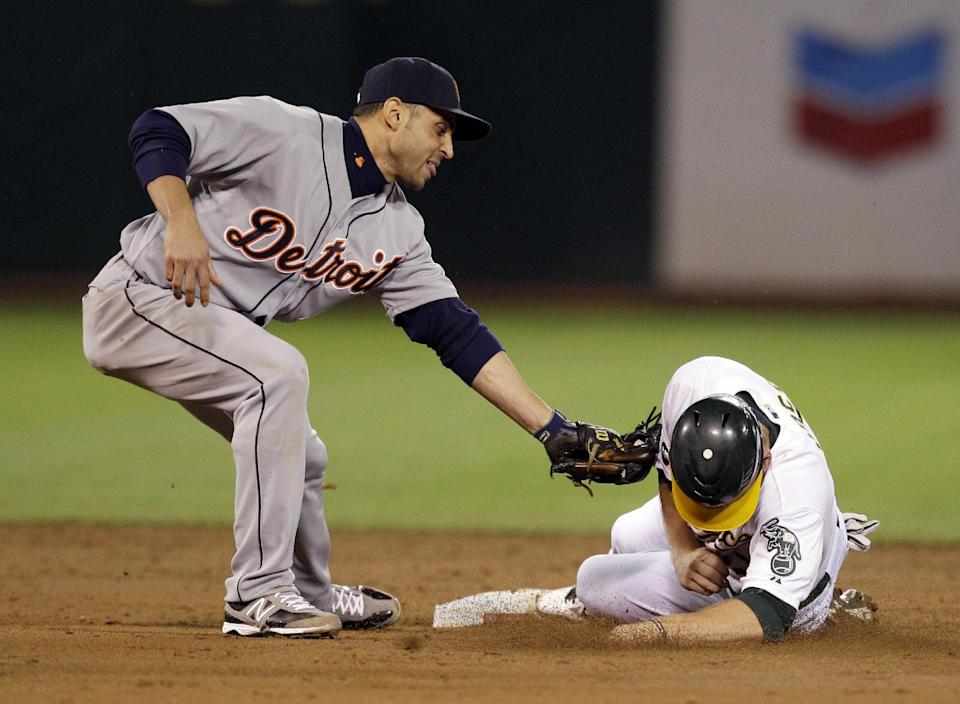 Detroit Tigers second baseman Omar Infante, left, tags out Oakland Athletics Brandon Moss on a steal attempt in the third inning of Game 5 of an American League division baseball series in Oakland, Calif., Thursday, Oct. 11, 2012. (AP Photo/Ben Margot)
