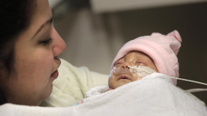 Haydee Ibarra, left, holds her 14-week-old daughter, Melinda Star Guido, at the Los Angeles County-USC Medical Center in Los Angeles, Wednesday, Dec. 14, 2011. At birth, Melinda Star Guido tipped the scales at only 9 1/2 ounces, a tad less than the weight of two iPhone 4S. Most babies her size don't survive, but doctors are preparing to send her home as soon as the end of the month. Melinda is believed to be the second smallest baby to survive in the United States and the third smallest in the world. (AP Photo/Jae C. Hong)