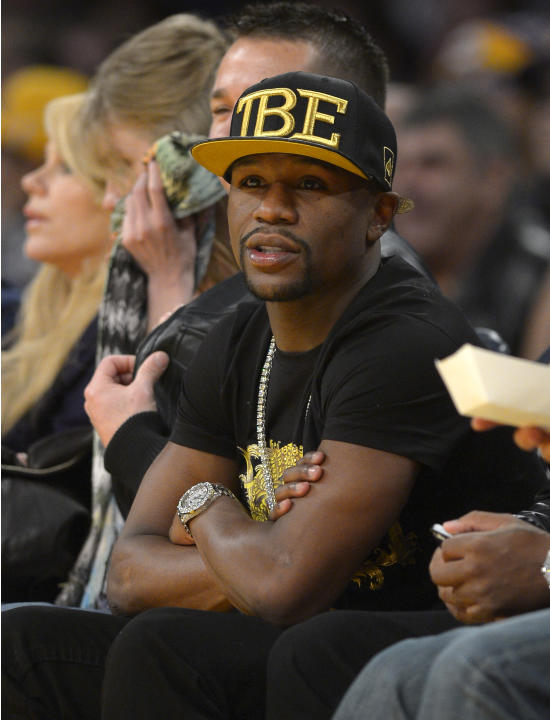 Boxer Floyd Mayweather Jr. watches the Los Angeles Lakers play the Sacramento Kings during the first half of an NBA basketball game, Sunday, Nov. 24, 2013, in Los Angeles