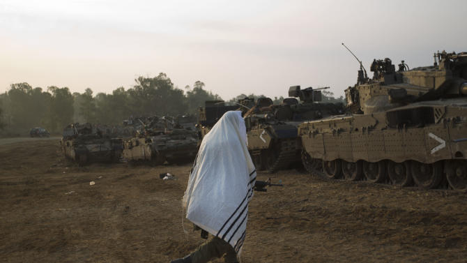 An Israeli soldier covered in a prayer shawl walks past tanks in a staging area near the Israel Gaza Strip Border, southern Israel, Monday, Nov. 19, 2012. The Palestinian civilian death toll mounted Monday as Israeli aircraft struck densely populated areas in the Gaza Strip in its campaign to quell militant rocket fire menacing nearly half of Israel's population. (AP Photo/Ariel Schalit)