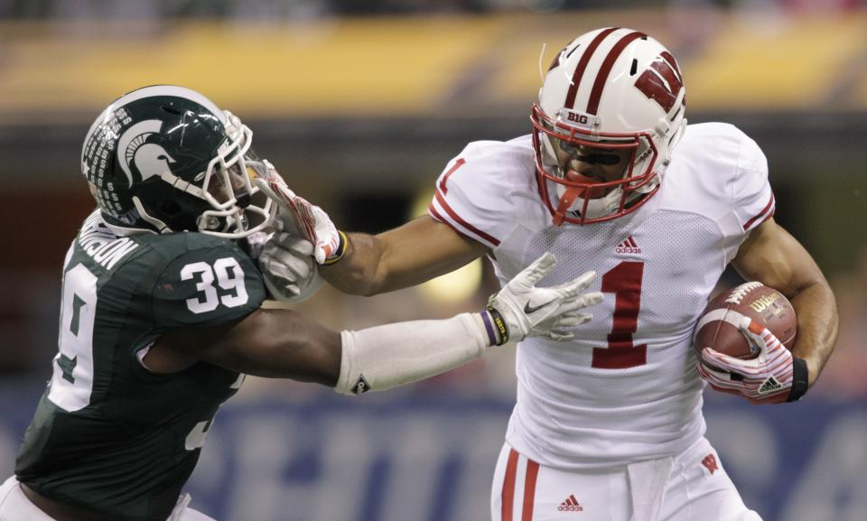Wisconsin's Nick Toon runs against Michigan State's Trenton Robinson during the second half of the Big Ten conference championship NCAA college football game on Saturday, Dec. 3, 2011 in Indianapolis. (AP Photo/AJ Mast)