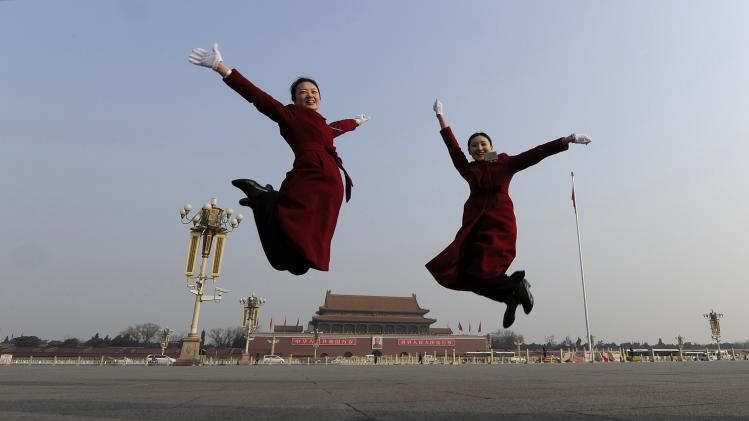 Hotel guides jump as they pose for photographs in front of the Tiananmen Gate and the giant portrait of Chinese late chairman Mao Zedong, near the Great Hall of the People during a plenary session of the National People's Congress (NPC) in Beijing