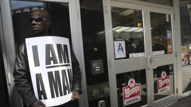 A demonstrator holds a sign outside of a Wendy's fast food restaurant, Thursday, April 4, 2013 in New York.  New York City fast food workers plan a second job action day to press for higher wages. Organizers say hundreds of workers plan to demonstrate Thursday at dozens of fast food establishments, including McDonald's, Domino's, Wendy's and Pizza Hut. (AP Photo/Mary Altaffer)
