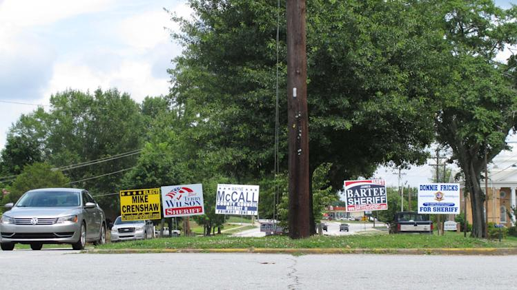 In this June 6, 2012 photo, signs for all four sheriff's candidates in Oconee County stand on display in a median in Walhalla, S.C. The race for sheriff has gotten nasty, with investigators saying one candidate tried to kidnap a man trying to kick him out of the race. (AP Photo/Jeffrey Collins)