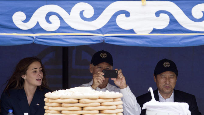 U.S. Vice President Joe Biden, center, accompanied by his granddaughter Naomi Biden, left, and Mongolian Prime Minister Sukhbaatar Batbold, left, uses a mobile phone to take pictures during Mini Nadam or Mongolian wrestling performance in Ulan Bator, Mongolia, Monday, Aug. 22, 2011. (AP Photo/Andy Wong)