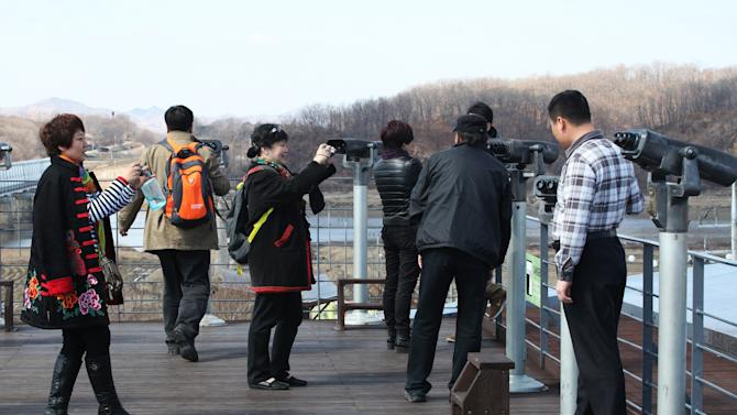 Chinese tourists take souvenir pictures at Imjingak Pavilion in Paju near the demilitarized zone between the two Koreas, South Korea,Thursday, March 14, 2013.  Busloads of tourists still show up to gawk at the world's most heavily fortified border, even as governments on both sides threaten to reduce each other to rubble. (AP Photo/Ahn Young-joon)