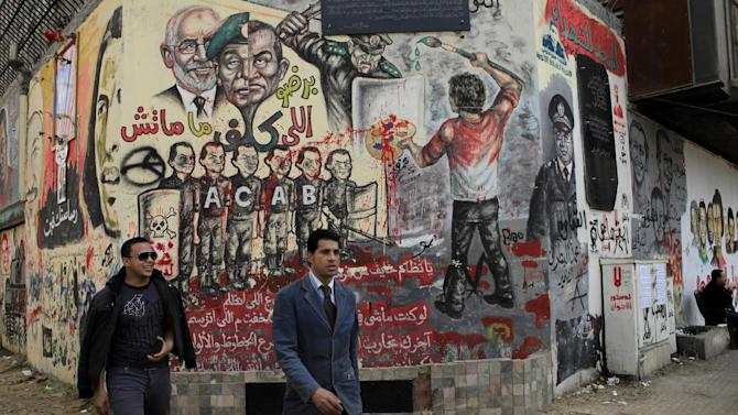 Egyptian walk past revolutionary graffiti in Tahrir Square, Cairo, Egypt, Friday, Jan. 25, 2013. Egyptian opposition protesters are gathering in Cairo's Tahrir Square to mark the second anniversary of the uprising that toppled Hosni Mubarak's autocratic regime. (AP Photo/Thomas Hartwell)