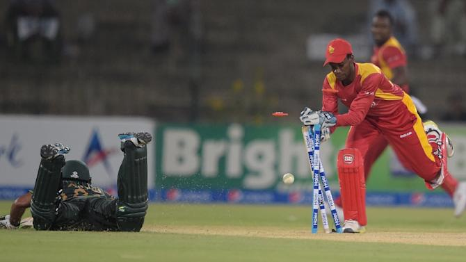 Zimbabwe's wicketkeeper Richmond Mutumbami (R) makes an unsuccessful attempt to run out Pakistan's Asad Shafiq during the second One Day International cricket match in Lahore on May 29, 2015