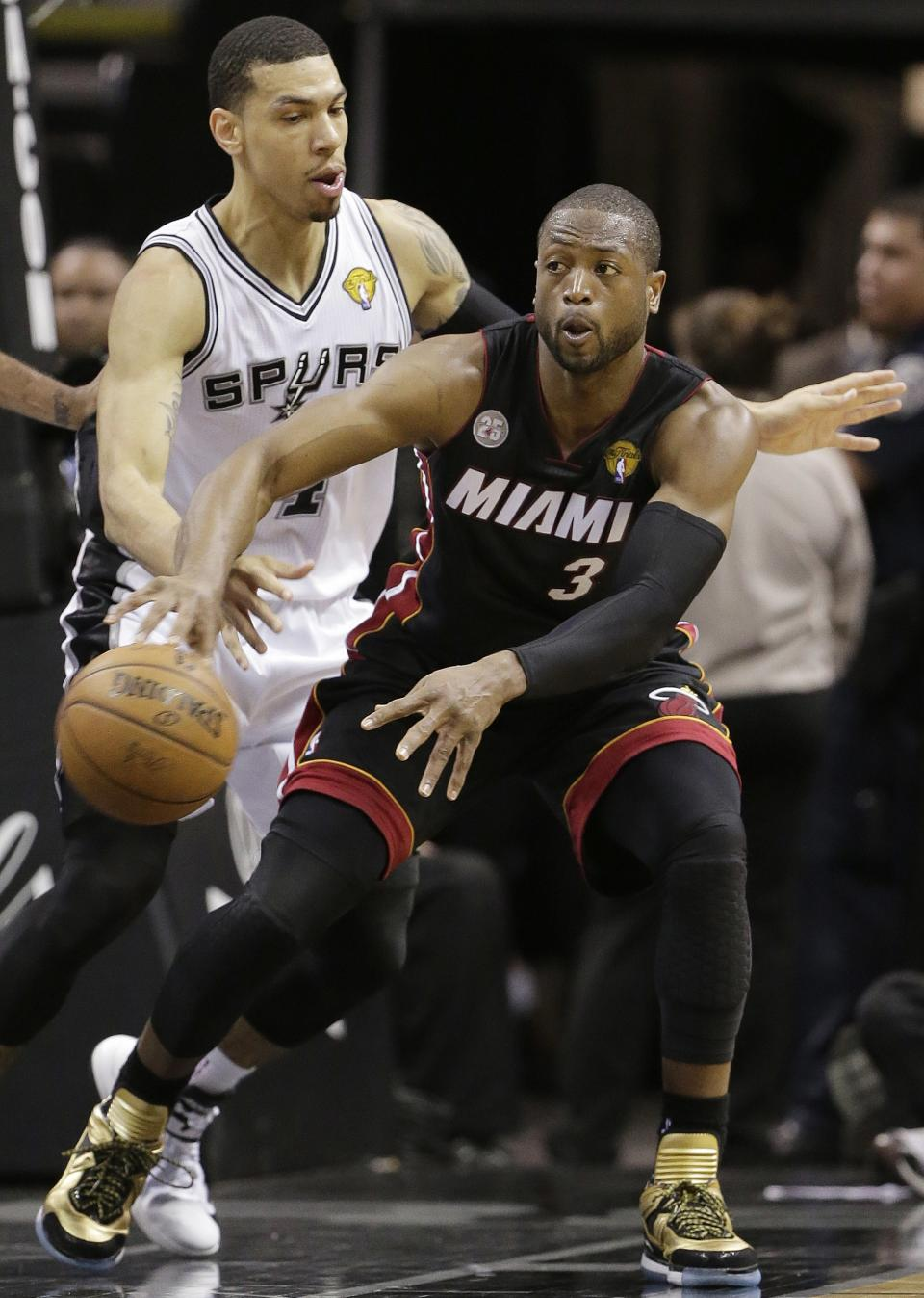 Miami Heat's Dwyane Wade (3) passes around San Antonio Spurs' Danny Green (4) during the first half at Game 5 of the NBA Finals basketball series, Sunday, June 16, 2013, in San Antonio. (AP Photo/Eric Gay)