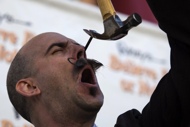 A performance artist pulls a nail out of his nasal cavity ahead of the annual World Sword Swallower's Day celebrations outside the Ripley's Believe It or Not! museum in Los Angeles