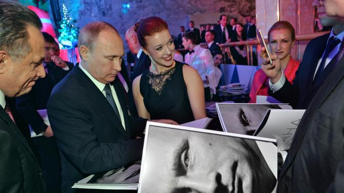 Russian President Vladimir Putin signs autographs on a photo book after a New Year reception in Moscow's Kremlin