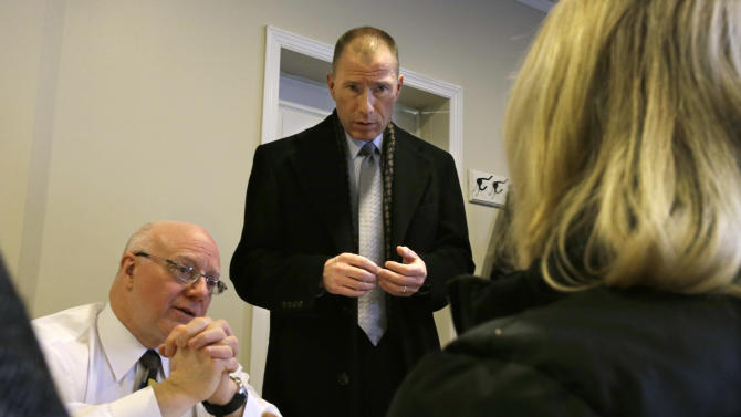 "Ken Kobylowski, standing, Commissioner New Jersey Department of  Banking and Insurance looks on as New Jersey Department of  Banking and Insurance employee, Christian Traum, left, listens to a resident at a center in Union Beach, N.J., Tuesday, Feb. 5, 2013. New Jersey Gov. Chris Christie visited the center and told a gathering that the National Flood Insurance Program's handling of claims in New Jersey has been ""a disgrace,"" complaining that the program has been far too slow to resolve claims from Superstorm Sandy, with 70 percent of cases unresolved three months after the disaster. (AP Photo/Mel Evans)"